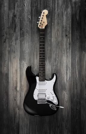 acoustical: Black electric guitar on wooden background.