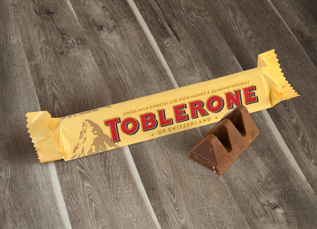 Chisinau, Moldova - June 14, 2016: A bar of Toblerone - Swiss milk chocolate with honey and almond nougat on a wood background. With clipping path.