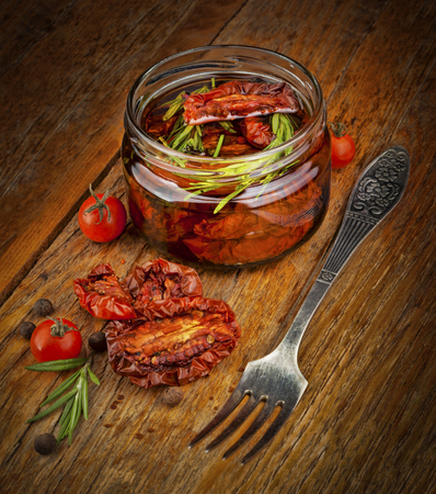 natural moody: Delicious dried tomatoes in the jar of olive oil, the fork on wood background. In rustic style.