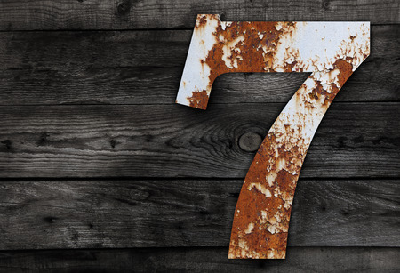 metal alphabet: Old rusty metal alphabet, text 7 on Wooden Background nails.