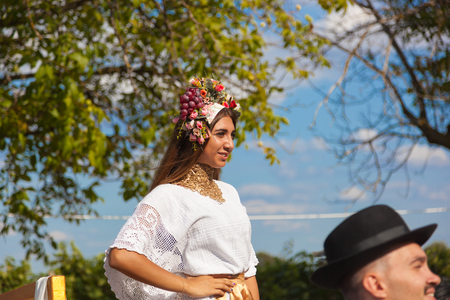 CHISINAU, MOLDOVA- SEPTEMBER 7, 2017: Parade participants in folk costumes. Beautiful woman with flower wreath on her head. Must Fest 2017 wine festival. Cricova company in the production of wine. National holiday