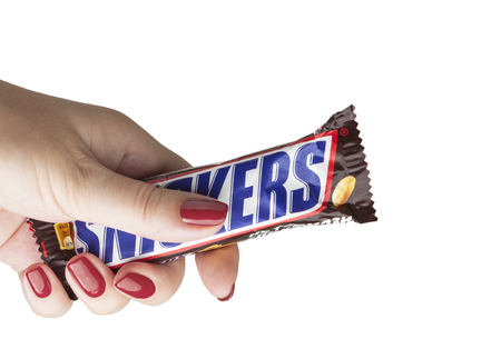 CHISINAU, MOLDOVA - December 21, 2017: Hand holding a Snickers chocolate bar. Snickers bars are produced by Mars Incorporated. Snickers was created by Franklin Clarence Mars in 1930 Editorial