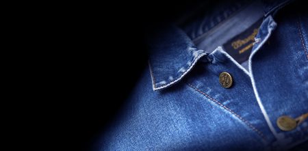 CHISINAU, MOLDOVA - December 25, 2017: Jeans jacket Wrangler blue color, isolated on black background. The Wrangler brand is owned by VF Corporation of Greensboro, North Carolina USA. Blurred concept
