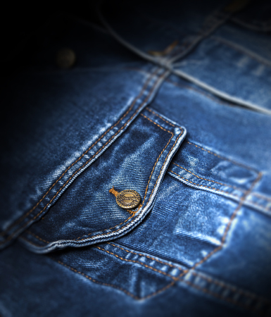 CHISINAU, MOLDOVA - December 25, 2017: Jeans jacket Wrangler blue color. Pocket closeup. The Wrangler brand is owned by VF Corporation of Greensboro, North Carolina USA. Blurred concept