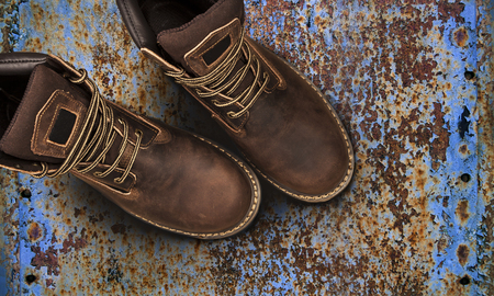 Mens brown boots on old rusty background. Closeup isolated Stock Photo