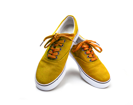 A pair of yellow color canvas shoes isolated on white background with clipping path