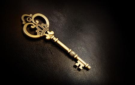 Old bronze key on a dark background