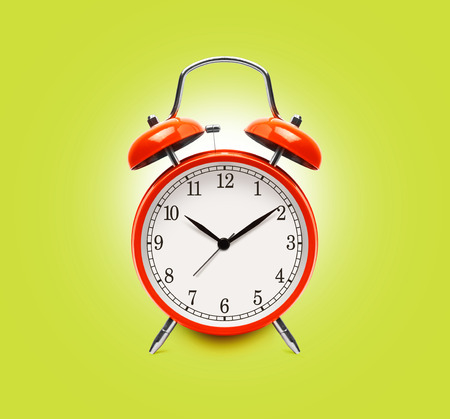 Red alarm clock isolated on yellow background