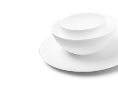 Set of white dishes on table on light background. Stock fotó