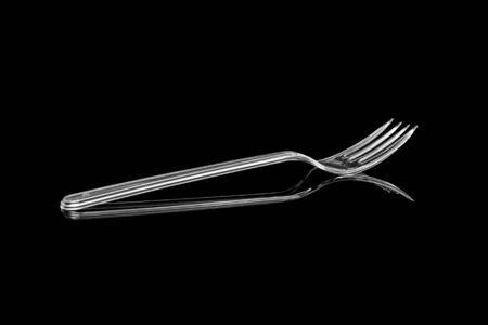 Transparent plastic fork isolated on black background.