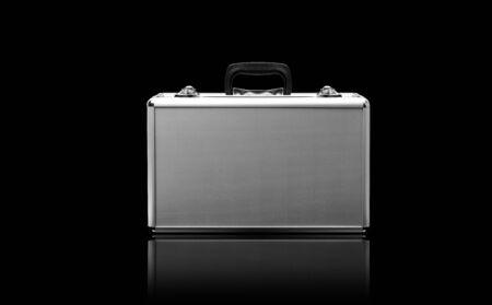 Metallic suitcase isolated on black background.