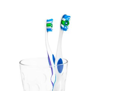 Toothbrushes in glass isolated on white background.