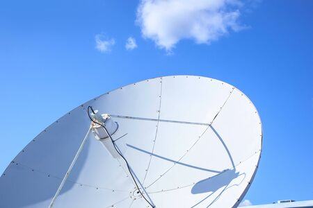 White big parabolic satellite antenna for telecommunications on a background of blue sky.