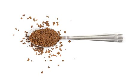 Spoon with instant coffee granules on a white background, top view