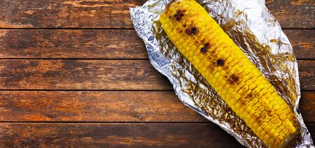 Tasty grilled corn on brown wooden table