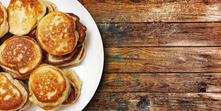 A pile of freshly baked pancakes lay on a plate isolated on wooden table Banque d'images