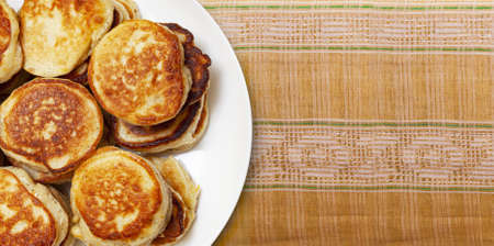 CHISINAU, MOLDOVA - May 18, 2020: Pile of freshly baked pancakes lay on a white plate on a folk embroidery fabric handmade close up. Top view Éditoriale