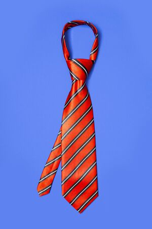Red men's striped tie taken off for leisure time, isolated on blue background.