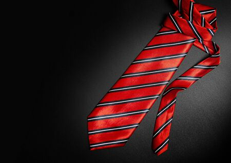 Red men's striped tie isolated on black