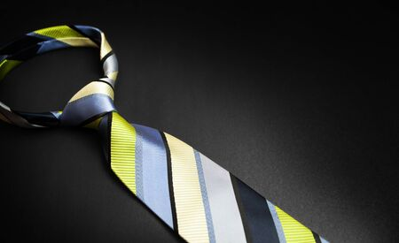 Men's striped tie in different colors isolated on black background. Banque d'images