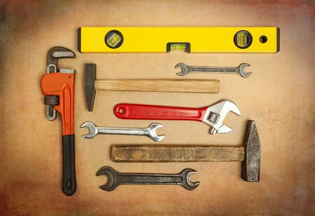 Various tools to work with, hammer, spanner, gas wrench, level to measure the level. Close-up on a background of craft paper