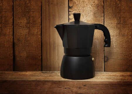 Black Italian coffee maker geyser isolated on wooden background