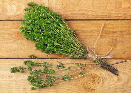 bunch of thyme twigs isolated on wooden table
