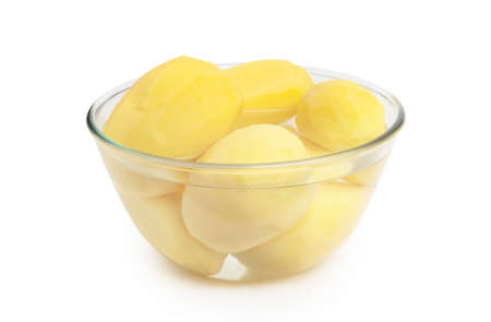 Peeled potatoes in a glass bowl isolated on white background. Banco de Imagens