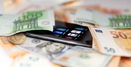 Mobile banking and finance concept: smartphone with applications, euro, US dollar banknotes, and bitcoin. Business background. Blurred concept Banco de Imagens