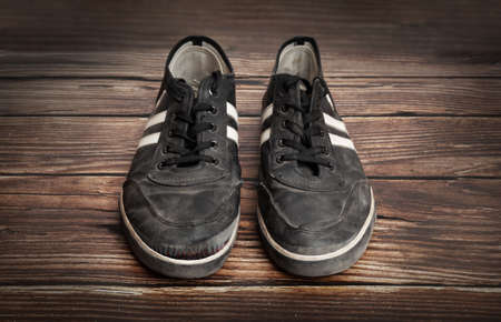 Dirty old black sneakers isolated on a wooden plank background