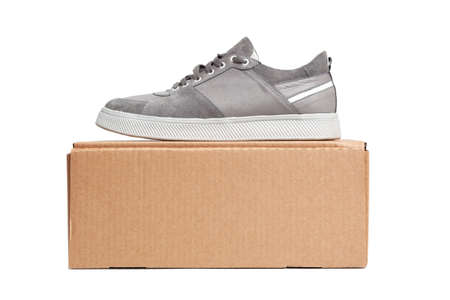 Gray casual sports shoes, sneaker on a brown cardboard box isolated on a white background Banco de Imagens