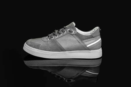 Gray casual sports shoes, sneaker isolated on a black background