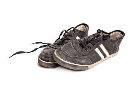 Dirty old black sneakers isolated on a white background Banco de Imagens