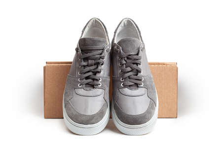 Gray casual sports shoes, sneaker isolated on a brown cardboard box isolated on a white background Banco de Imagens