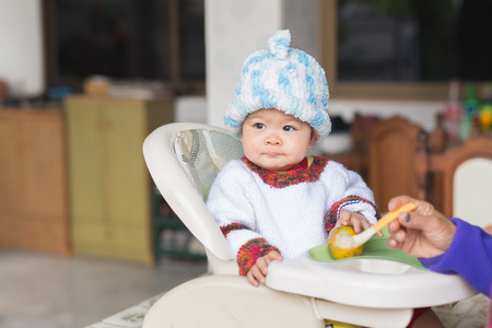 asia food: the baby learns to eat by himself. he can use spoon well. so he is very happy (focus at his face) Stock Photo