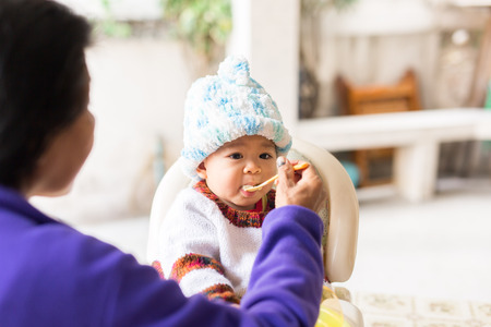 baby on hands: the baby learns to eat by himself. he can use spoon well. so he is very happy (focus at his face) Stock Photo