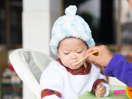das Baby lernt, indem er sich zu essen. er kann Löffel gut verwenden. so ist er sehr glücklich (Fokus auf sein Gesicht)