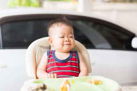 the baby learns to eat by himself. he can use spoon well. so he is very happy (focus at his face) Banco de Imagens