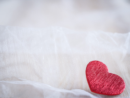 Red heart on a soft white textile background 免版税图像