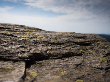Rock with lichen and blue cloudy sky background Imagens