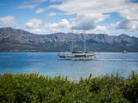 Sailing boat passing a shore of Hvar island, Croatia on sunny summer day, view of mountains and fresh green grass Stock Photo