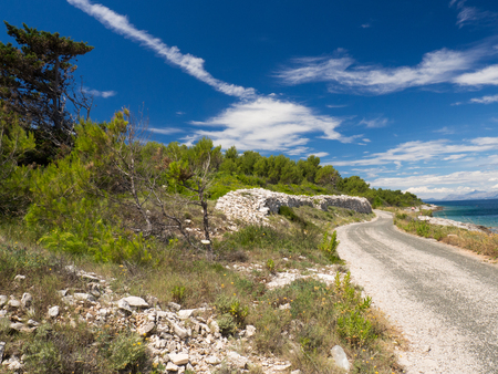 The way around the beautiful coast on Hvar island, Croatia with fresh green grass, blue sky and mountains