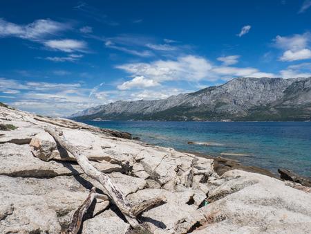View of stone shore with dry tree branch lying on a coast, Hvar island, Croatia Stock Photo