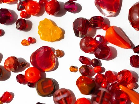 Sparkling colorful beads in various red colors in detail on white background