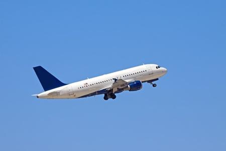 A passenger plane ascends into the blue sky. Stock Photo