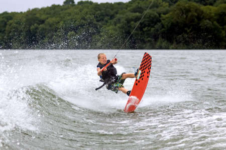 A young wakeboarder hits the water after a jump photo