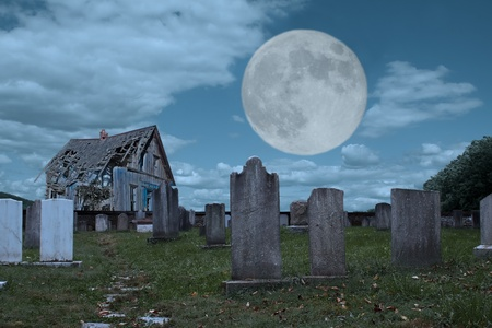 A graveyard and dilapidated building in the moonlight photo