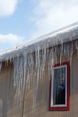 Icicles hanging from a roof on a sunny winter day