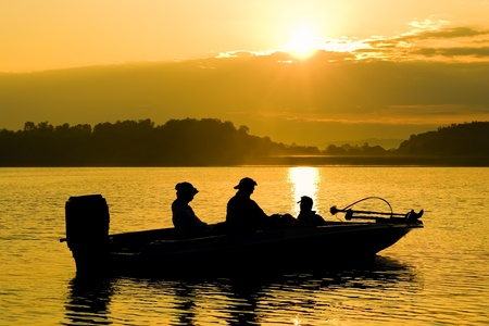 yellow boats: Fishermen boating on a lake at sunrise