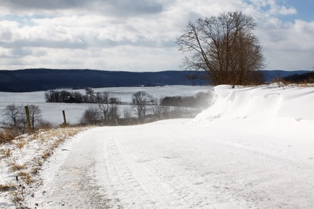 Snow blowing over a rural Pennsylvania road. Stock Photo - 12525233